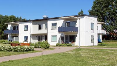 Lägenhetshus i två våningar med balkonger och uteplatser i markplan