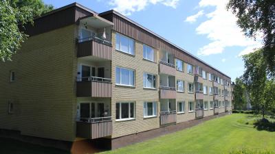 Bild som visar ett gult tegelhus i tre våningar och bruna balkongfronter. Platt tak med brun takfot. bilden tagen på husets baksida med gräsmatta bakom huset.