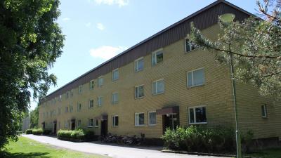 Bild som visar ett gult tegelhus i tre våningar och med fem ingångar. Platt tak med brun takfot.