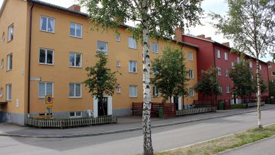 Bild på två lägenhetshus i puts. Husen har tre våningar.
