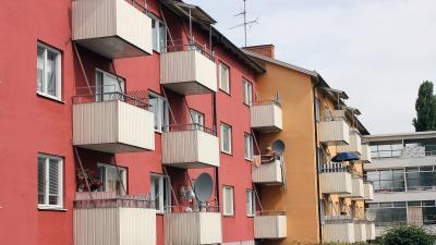 Bild på trevånings lägenhetshus i puts.