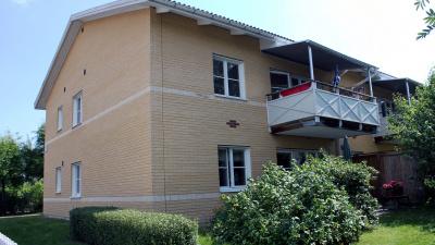 Bild på ljust lägenhetshus i tegel i två våningar. Lägenheterna har egen ingång.