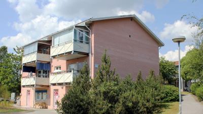 Bild på rosa tegelhus, ett lägenhetshus i suterräng med lokal i bottenplan.