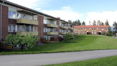Bild på lägenhetshus i tegel och suterräng. Tre våningar och lägenheterna på markplan har uteplats.