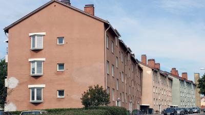 Bild på avlångt lägenhetshus i puts i tre sektioner. Husen har tre våningar.