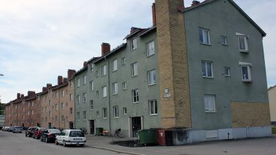 Bild på lägenhetshus i puts, tre våningar.
