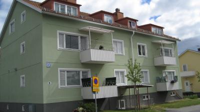 Bild på grönt lägenhetshus i puts.
