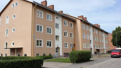Tre våningar högt flerbostadshus i stenputs.