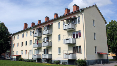 Bild på trevånings lägenhetshus i vit puts och blå balkonger.