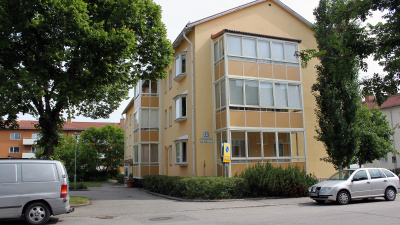 Bild på gult lägenhetshus i puts med inglasade balkonger och tre våningar.