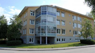 Lägenhetshus i tre våningar med både inglasade balkonger och fransk balkong.