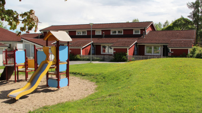 Bild på innergård på bostadsområde med lekplats, gräsmatta och hyreshus.