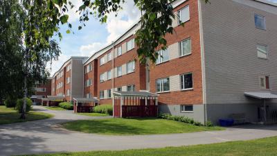Bild på rött tegelhus i tre våningar.