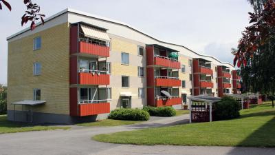 Bild på gult tegelhus i tre våningar med röda balkonger.