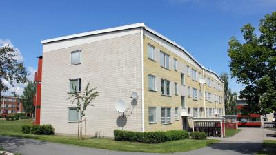 Bild på lägenhetshus i tre våningar i gult och vitt tegel.