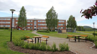 Bild med lägenhetshus i tre våningar i bakgrunden och bänkar och bord i förgrunden.