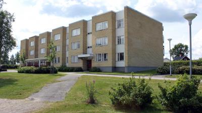 Bild på gult tegelhus i tre våningar. Gräsmatta och buskar i förgrunden.