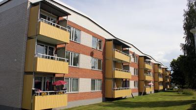 Bild på rött tegelhus i tre våningar med gula balkonger.