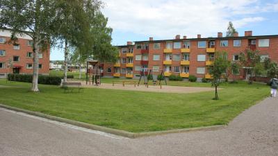 Bild tagen på håll med gräsmatta och lekplats i förgrunden. I bakgrunden två lägenhetshus i tre vå våningar och rött tegel.