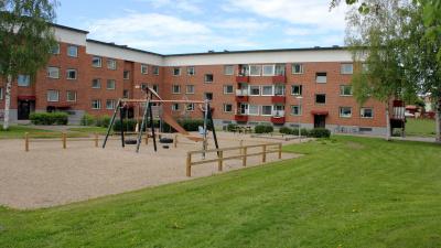 Bild på lekplats i förgrunden och och i bakgrunden ett tegelrött lägenhetshus med röda balkonger i tre våningar.
