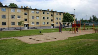 Bild på lekplats i förgrunden och och i bakgrunden ett gult lägenhetshus i tre våningar.