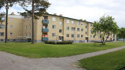 I förgrunden gräsmatta med grusgångar och i bakgrunden gult lägenhetshus i tre våningar.