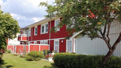 Bild på lägenhetshus i två våningar. Rött trähus med uteplats i markplan.