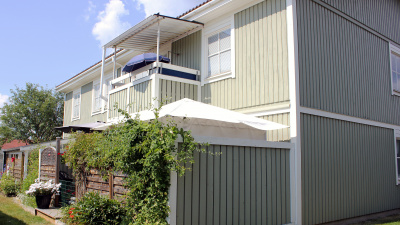 Bild på lägenhetshus i två våningar. Grönt trähus med uteplats i markplan.