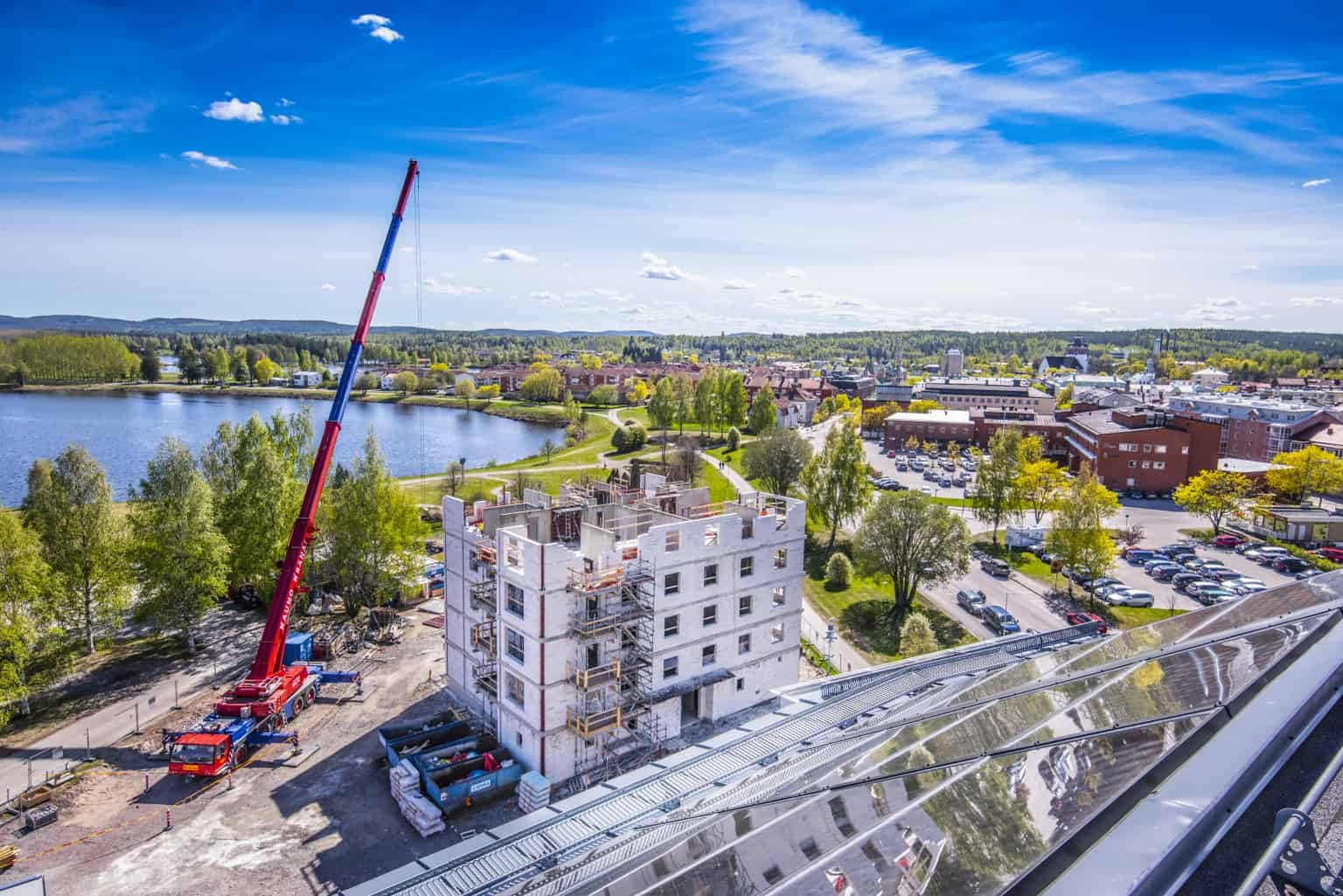 Flerbostadshus under uppbyggnad.. Fotot är taget uppifrån och du ser en byggkran och Bollnäs stad i bakgrunden.