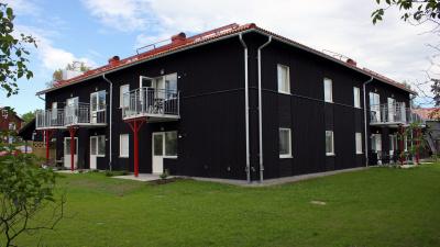 Lägenhetshus med svart träpanel. Balkonger med ribbor på övervåning och uteplats i markplan.