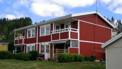 Tvåvånings lägenhetshus i trä. Balkonger på andra våningen och uteplatser i markplan.