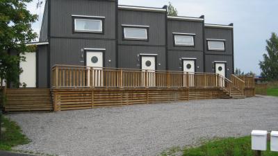 Flerbostadshus i grå träfasad med fyra lägenheter som sitter ihop som ett radhus,