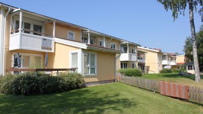 Lägenhetshus i två våningar med träfasad.