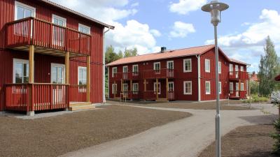 Bild på röda trähus med lägenheter i två våningar och egen ingång ifrån loftgång.