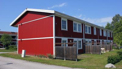Tvåvånings lägenhetshus med röd träfasad.