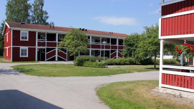 Tvåvånings lägenhetshus med röd träfasad. Egen ingång ifrån loftgång.