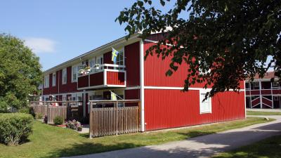Tvåvånings lägenhetshus med röd träfasad. Balkonger på andra våningen och uteplats i markplan.