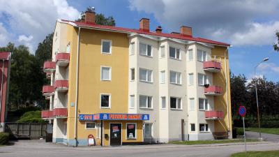 Bild som visar ett punkthus i tre våningar med putsad fasad och pizzeria i markplan.