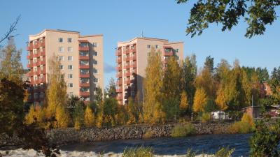 Punkthus med lägenheter, sju våningar högt med vanliga balkonger. Bilden är tagen på håll med älven Ljusnan i förgrunden.