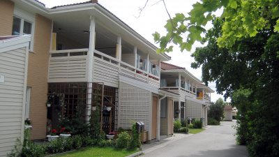 Lägenhetshus i två våningar. Alla lägenheter har egen ingång och uteplatser i markplan.