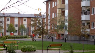 Innergård med grön gräsmatta, en parkbänk samt två flerbostadshus i tre våningar och rött tegel .