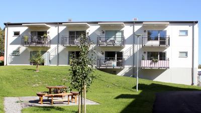 Vitt putshus med lägenheter, svarta balkonger med ribbor. Innergård med uteplats och grill.