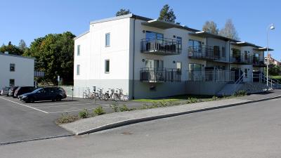 Vitt putshus med lägenheter, svarta balkonger med ribbor.