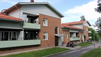 Bild på lägenhetshus i tegel.