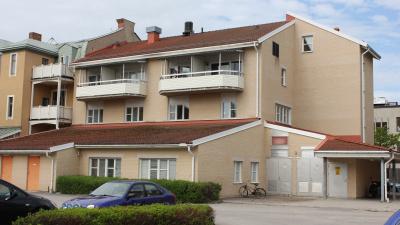 Lägenhetshus i tre våningar. åningar med inglasade balkonger och uteplatser i markplan.