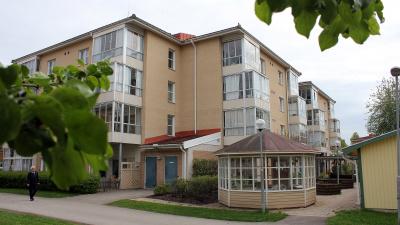 Lägenhetshus i tre våningar med inglasade balkonger och uteplatser i markplan. åningar med inglasade balkonger och uteplatser i markplan.
