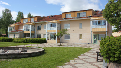 Bild på lägenhetshus i tre våningar med inglasade balkonger.