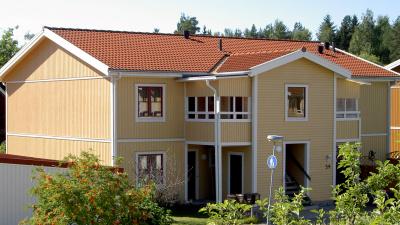 Bild på lägenhetshus i trä med egen ingång ifrån loftgång.