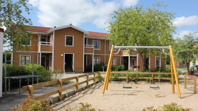 Lägenhetshus i trä med egen ingång ifrån loftgång. I förgrunden en gungställning.
