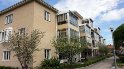 Lägenhetshus i tre våningar med inglasade balkonger.